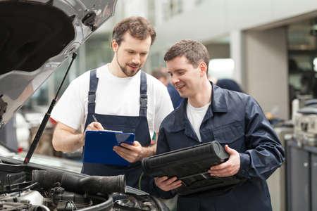 mecanico: Mec�nicos en el taller. Dos mec�nicos confidente que discute algo mientras uno de ellos la celebraci�n de un portapapeles Foto de archivo