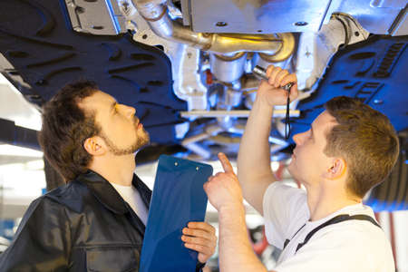 car shop: Two mechanics at work. Two confident auto mechanic working at the repair shop and discussing something while one of them holding a clipboard