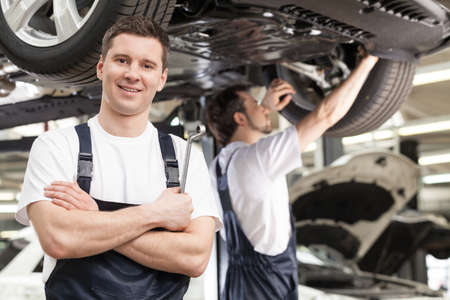 auto repair shop: Mechanics at work shop. Confident young mechanic standing with his arms crossed and smiling at camera while another one working on the background