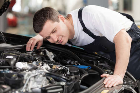 auto mechanic: Confident auto mechanic. Confident mechanic listening to the car engine working