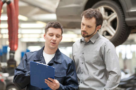 Mechanic and customer. Confident auto mechanic holding a clipboard and explaining something to a customer while standing near the car photo