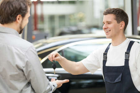 Auto mechanic and customer. Cheerful auto mechanic giving a car key to customer and smiling