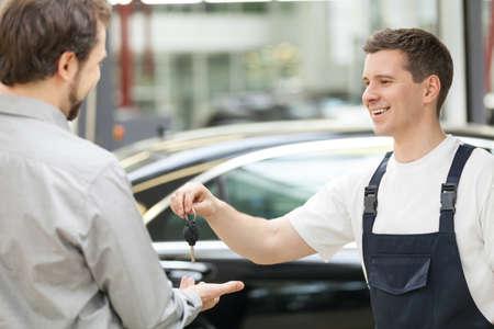 auto shop: Auto mechanic and customer. Cheerful auto mechanic giving a car key to customer and smiling