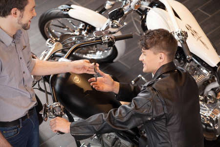 Buying a motorcycle. Top view of cheerful young sales executive giving the key to motorcycle owner photo