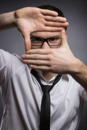 handcarves: Businessmen focusing  Young businessmen making a hand sign and looking at camera while isolated on grey