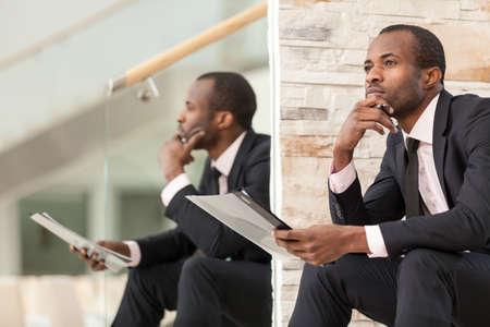 hombre pensando: Empresario se sienta y piensa con la barbilla en la mano