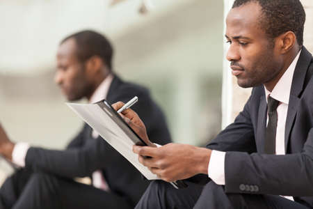 financial paperwork: Businessman sits and work with document Stock Photo