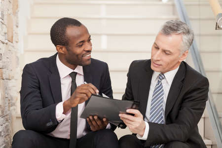 two people talking: Two businesspeople sitting on stairs and looking at papers. Stock Photo