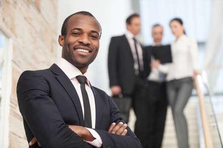 empresario: Sonriente hombre de negocios con sus colegas en el fondo