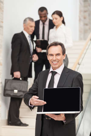 Mature businessman using laptop with executives at the back photo