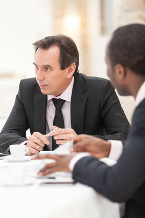 board room: Confident mid adult businessman listening to co-worker in conference room Stock Photo