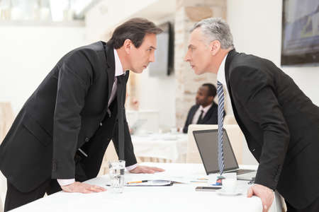 people fighting: Two businessmen are trying to come to an agreement.
