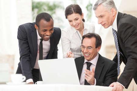 четыре человека: Счастливый деловых коллег, работающих вместе и обсуждать проект на ноутбуке во время встречи