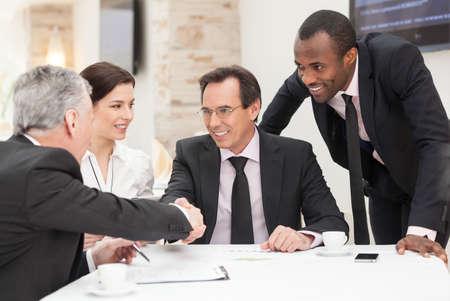 reuniones empresariales: Compa�eros de trabajo sentados en una mesa durante una reuni�n con dos ejecutivos hombres d�ndose la mano