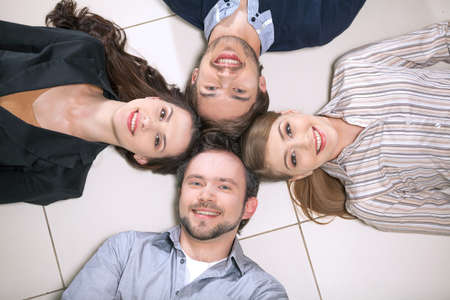 Top view of people laying together. Smiling holding heads together photo