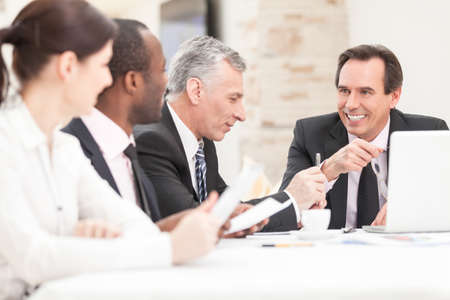 staff meeting: Smiling business people with paper work in board room - staff meeting