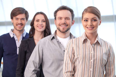 group leader: Group of people standing together. Looking at camera and smiling