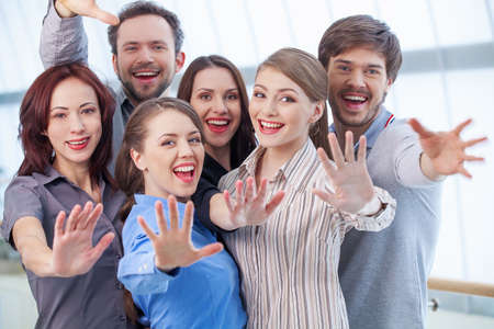 greets: Group of people showing their palm. Women and men standing together Stock Photo