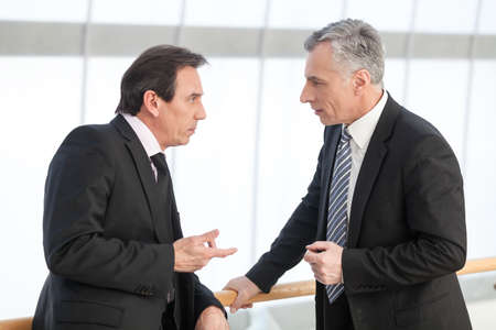 business relationship: Portrait of mature business man sharing his experience with associate