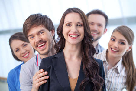 pleasant emotions: Young woman is leading a group of people. Looking at camera with big toothy smile Stock Photo