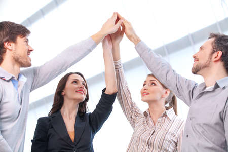 Business team is holding hands together. Raising one hand up Stock Photo