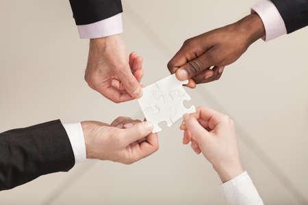 piezas de rompecabezas: Primer de los empresarios a poner cuatro piezas del rompecabezas. Top View. Cierre