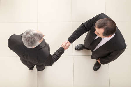 two on top: Businessmen shaking hands. Top View Stock Photo