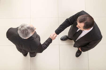 bridging: Businessmen shaking hands. Top View Stock Photo