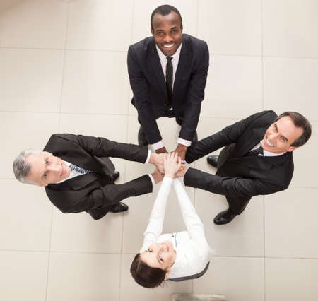 above 25: Union of successful businesspeople with hands on top of each other. Top View