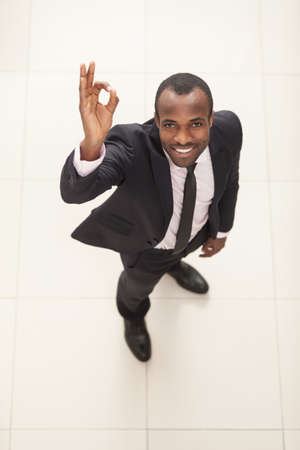 above 25: Above view of a successful businessman showing OK Sign. Top View Stock Photo