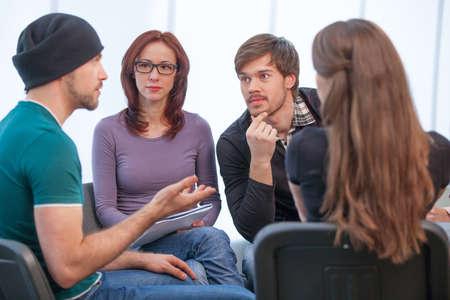 Groep mensen luisteren naar wat de jonge man zegt. Close-up van een aantal mensen in de werkplaats