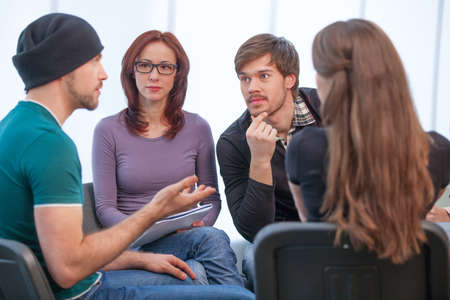 medium group of people: Group of people listening to what young man saying. Close up of several people in workshop Stock Photo