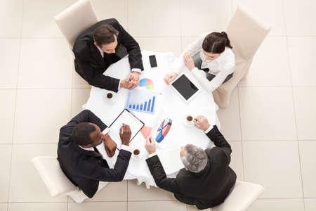 bovenaanzicht mens: Team achter bureau, het controleren van rapporten, praten. Top View