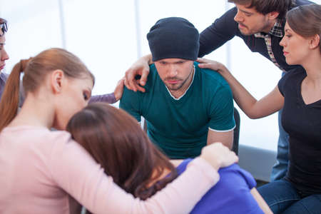 reassure: Several people comforting young man on background. Young woman comforting another woman on foreground