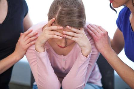 Twee vrouwen troostende schreeuwende meisje. Close-up van huilen meisje, die haar gezicht bedekt met beide handen Stockfoto