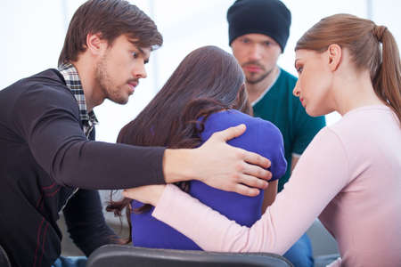 solace: Group of people comforting upset woman. Hugging from the both sides Stock Photo