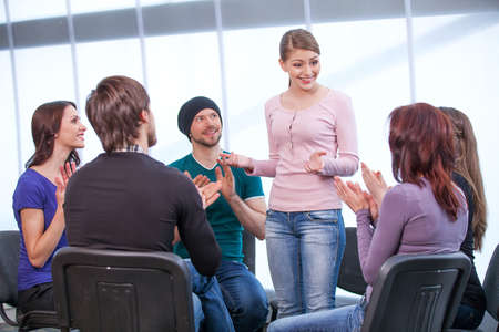 people clapping: Young girl is shearing her thoughts in a group of people. All clapping Stock Photo