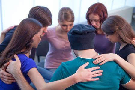 apoyo social: Grupo de personas que se sientan en un círculo. Abrazándose unos a otros