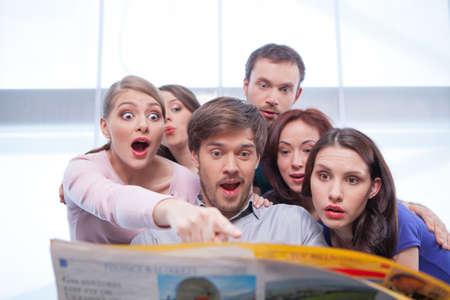 新聞を読んで若者のグループです。非常に驚いて、興味を探しています
