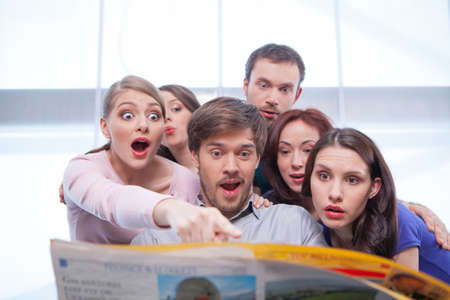 Group of young people reading newspaper. Looking very surprised and interested in Фото со стока