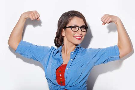 Femme forte. Belle jeune femme en montrant son musculature et en regardant la caméra isolée sur fond blanc