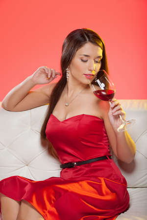 Woman drinking wine  Beautiful young woman in red dress sitting on the couch and drinking wine photo