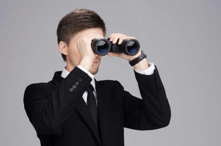 Geschäftsmann im Anzug schaut durch ein Fernglas mit grauem Hintergrund