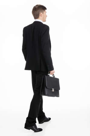 shot from behind: Adult businessman carrying a briefcase walking away