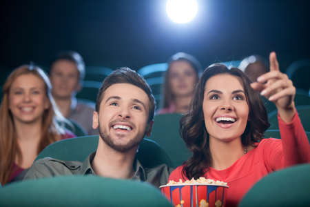 adult entertainment: Happy couple at the cinema. Cheerful young couple watching movie at the cinema Stock Photo