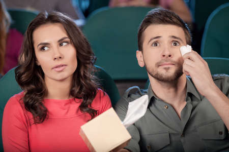 man crying: What a wonderful movie! Cheerful young couple watching movie at the cinema