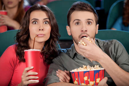 Exciting movie. Shocked young couple eating popcorn and drinking soda while watching movie at the cinema photo