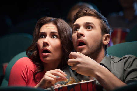 Horror movie. Terrified young couple eating popcorn while watching movie at the cinema photo