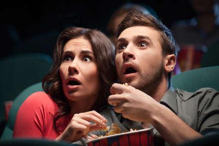 palomitas de maiz: Pel�cula de terror. Aterrorizado joven pareja comiendo palomitas de ma�z mientras ve la pel�cula en el cine Foto de archivo