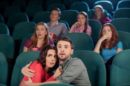 Horror movie. Terrified young couple hugging while watching movie at the cinema photo